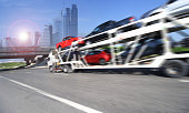 Trailer transports cars on highway with big city background