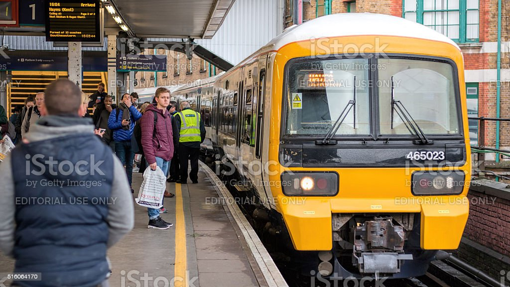 Train Arrives At City Railway Station Platform With Waiting Passengers. stock photo