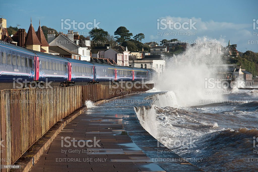 Train arriving at Dawlish with a wave breaking over it stock photo