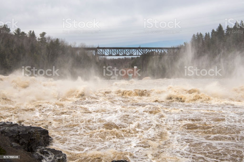 Train bridge across a raging river stock photo