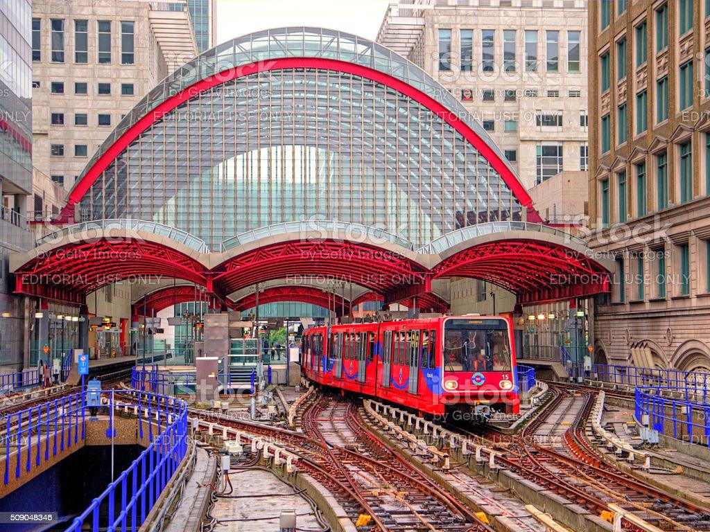 DLR train departs distinctive Canary Wharf station in rain stock photo