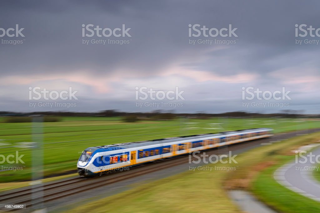 Train driving in a rural landscape during a dark day stock photo