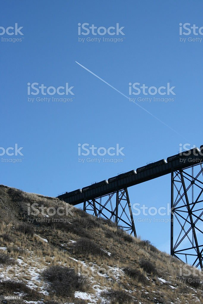 train going across bridge and jet in blue sky above royalty-free stock photo
