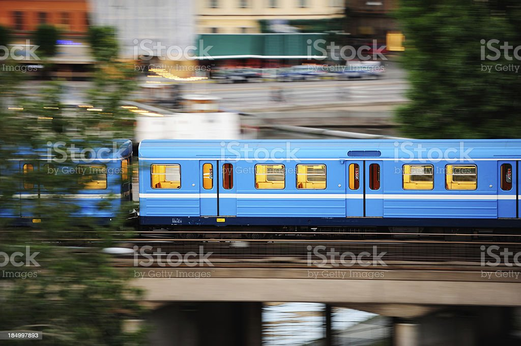 Train in profile on bridge and green trees stock photo