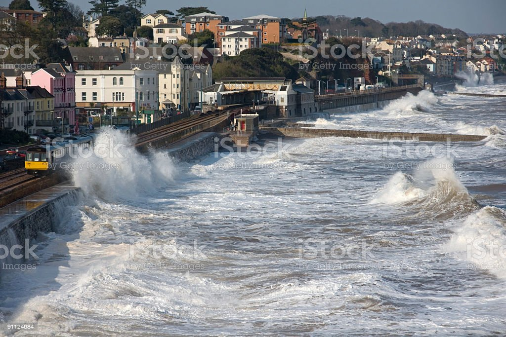 Train leaving Dawlish station in a storm stock photo