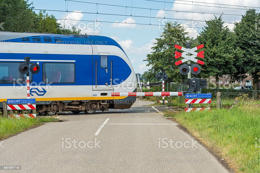 Train moving at high speed on a level crossing stock photo