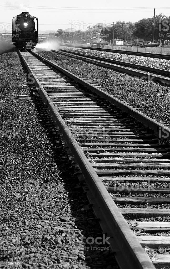Train moving down the tracks, black and white. stock photo