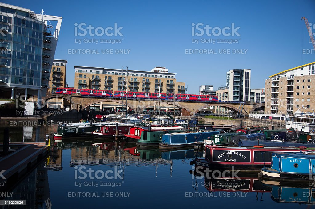 DLR Train on Viaduct passes Canal Boats stock photo