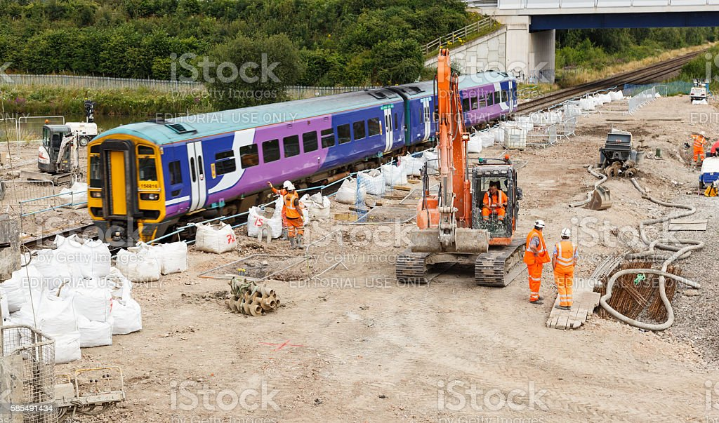 train passes by construction workers stock photo