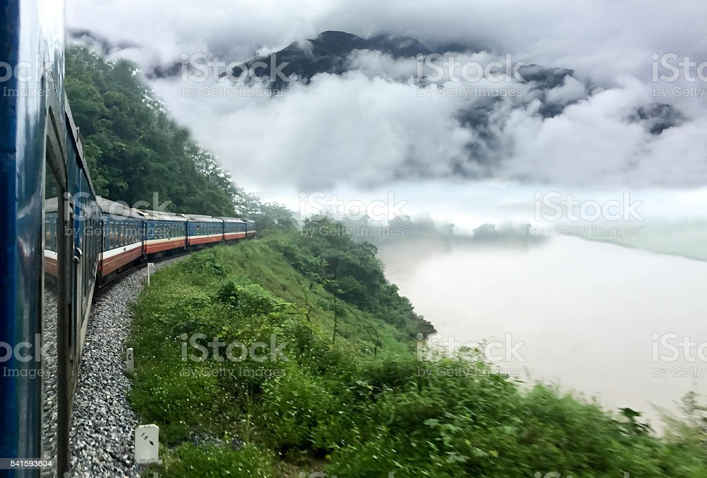 Train passing a beautiful fog mountains and  river stock photo