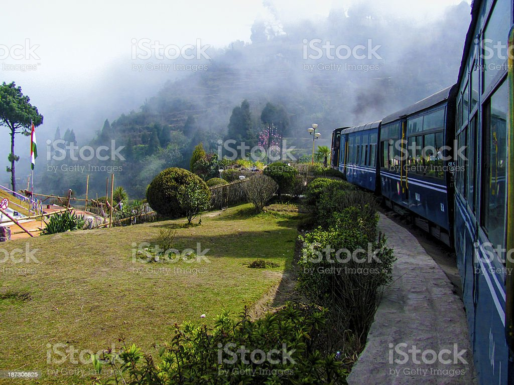 Train passing a garden and entering fog stock photo