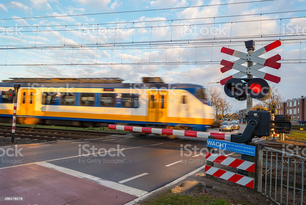 Train passing a rail crossing in a city stock photo
