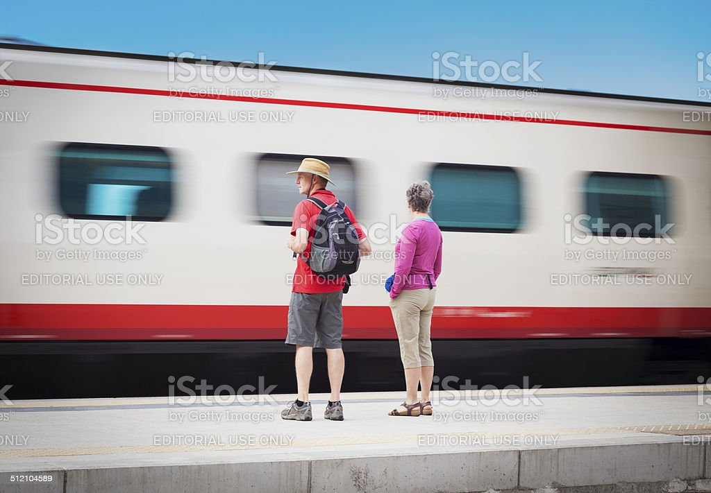 Train Passing By A Couple Of Tourists stock photo