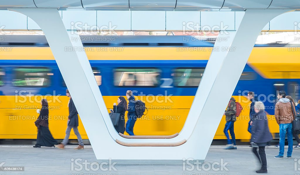 Train passing passengers on the platform at the station stock photo