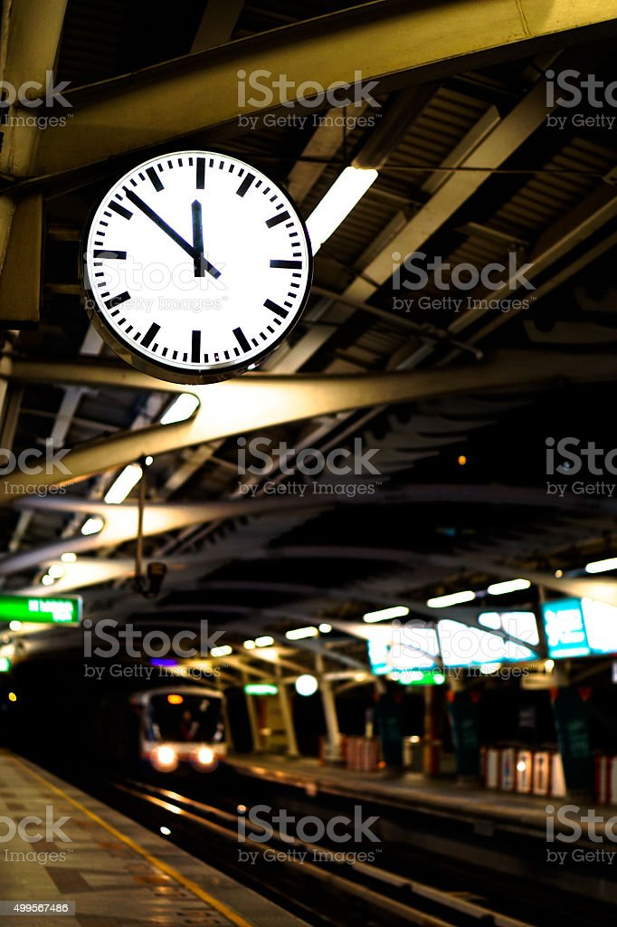 Train platform with clock at midnight, time or transportation abstract stock photo