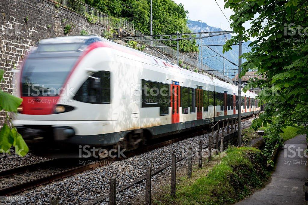 Train speeding on railroad track, Switzerland stock photo