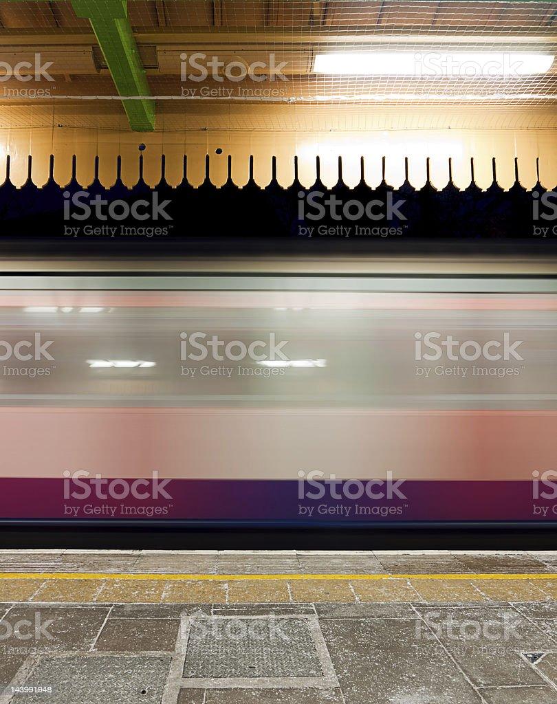 Train speeding through station at night, London, UK stock photo
