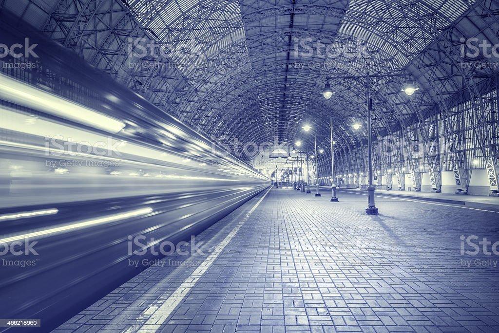 A train speeds through a station stock photo