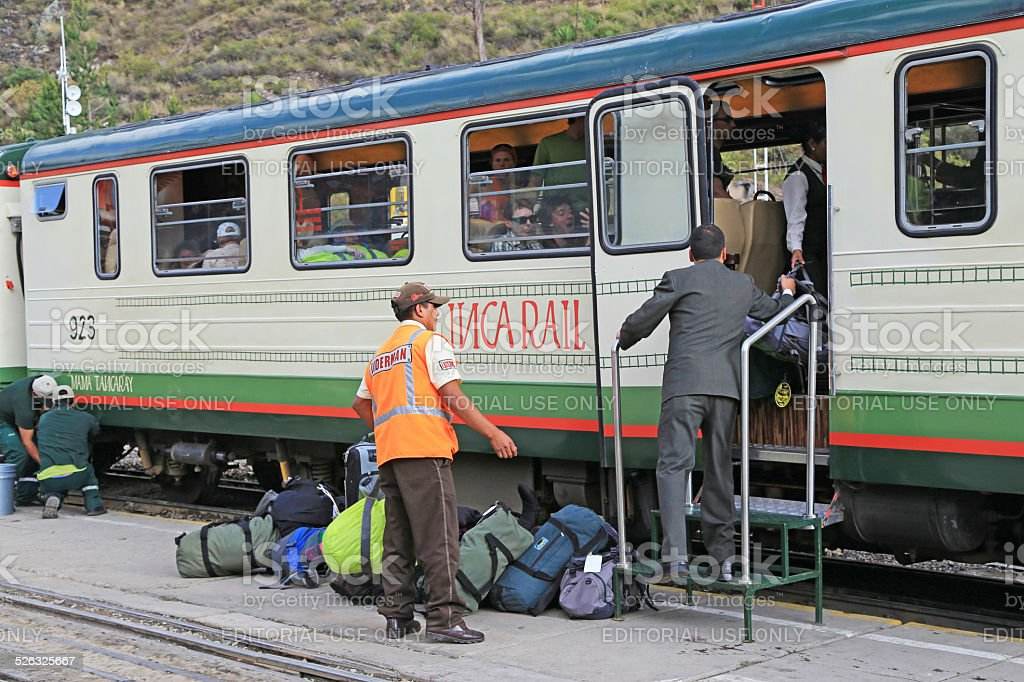 Train station officers loading tourists luggages into Inca Rail Train stock photo