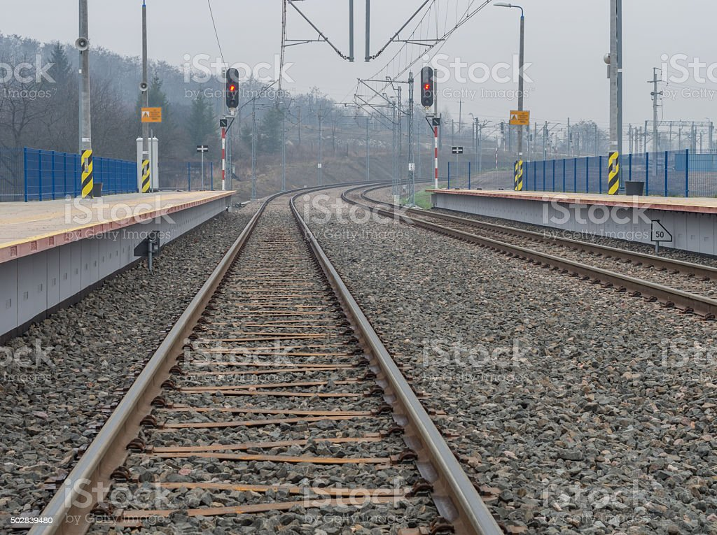 Train stop with double electrified railway track with railway signals stock photo