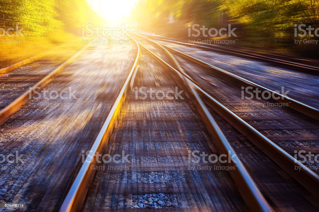 Train tracks leading into sunlight stock photo