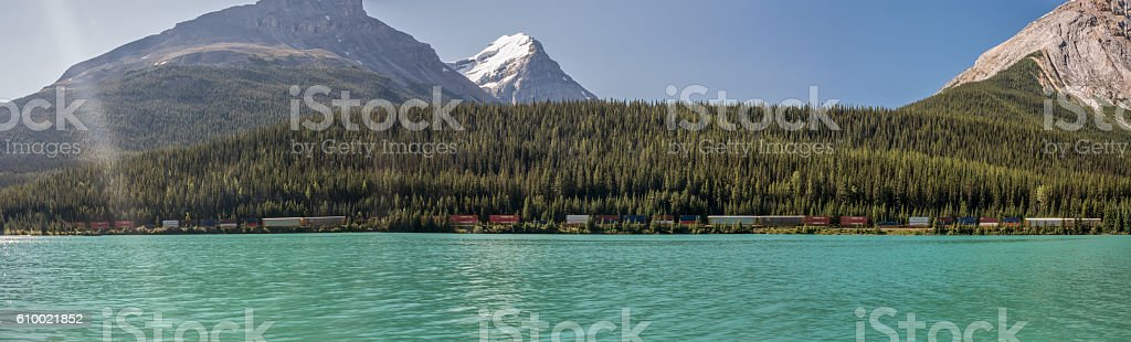 Train Travelling on the Shore of a Mountain Lake stock photo