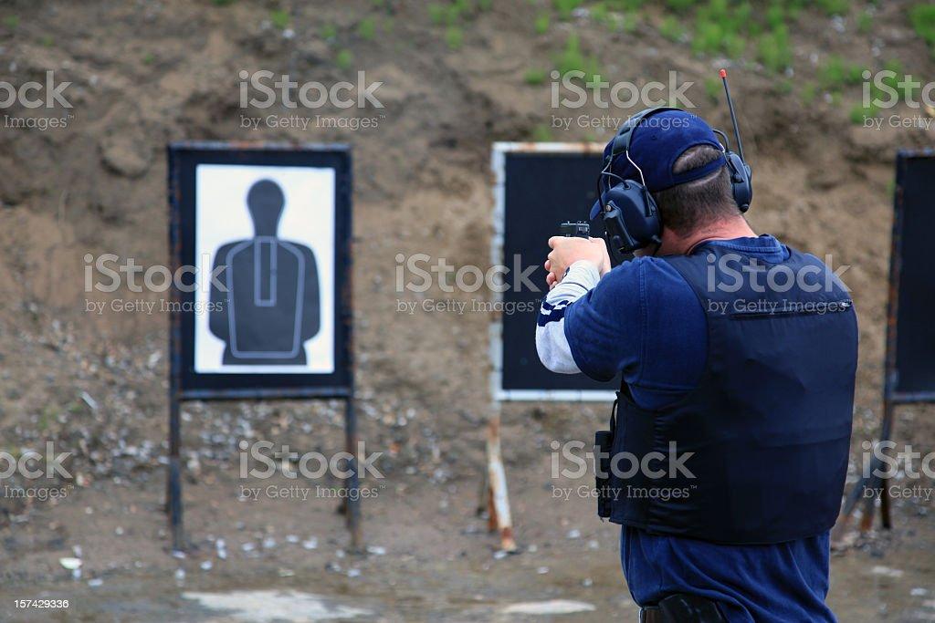 Trained man shooting a 9mm handgun at gun range royalty-free stock photo