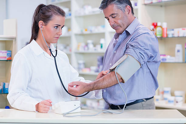 trainee listening to patients pulse with stethoscope stock photo - Pharmacist Trainee