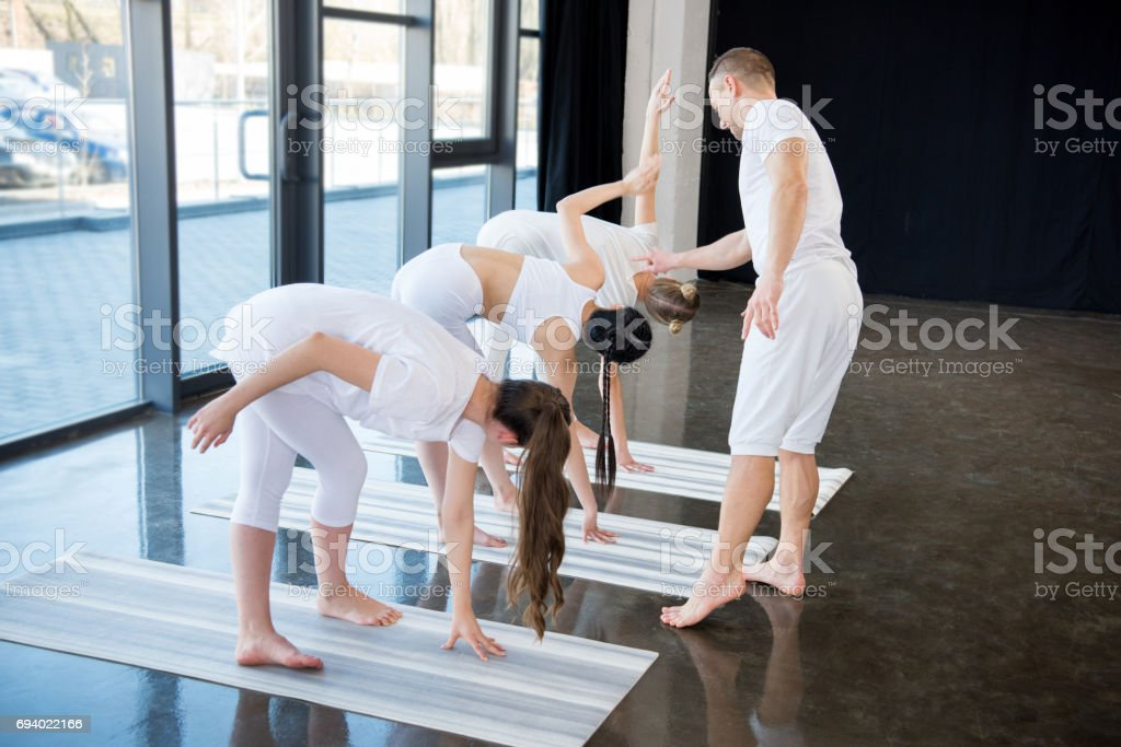 Trainer and young women practicing yoga on mats indoors stock photo