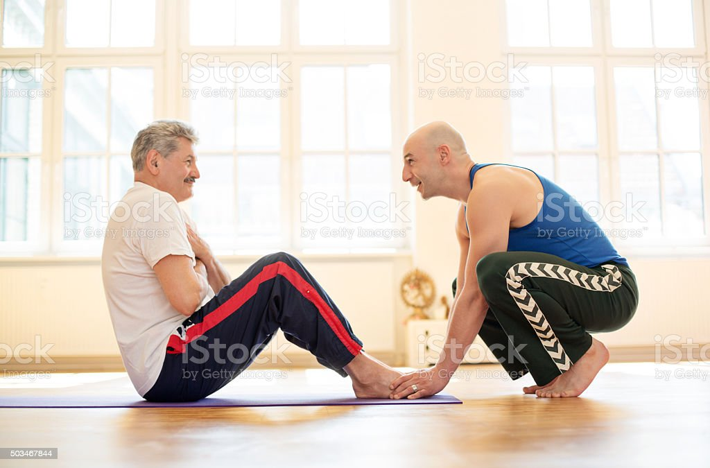 Trainer assisting man to perform sit ups stock photo
