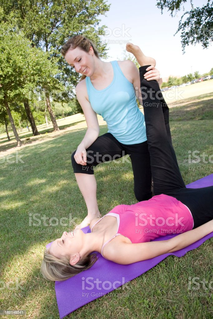 Trainer Helping Student do leg stretches royalty-free stock photo