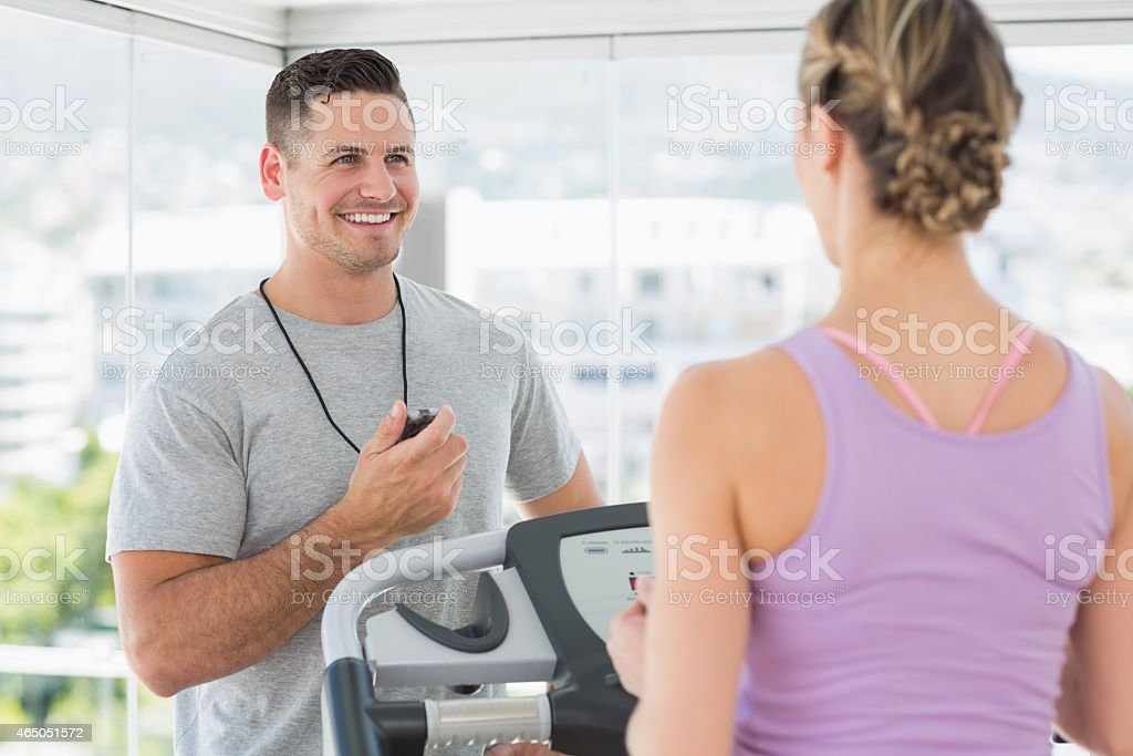 Trainer helping woman on treadmill stock photo