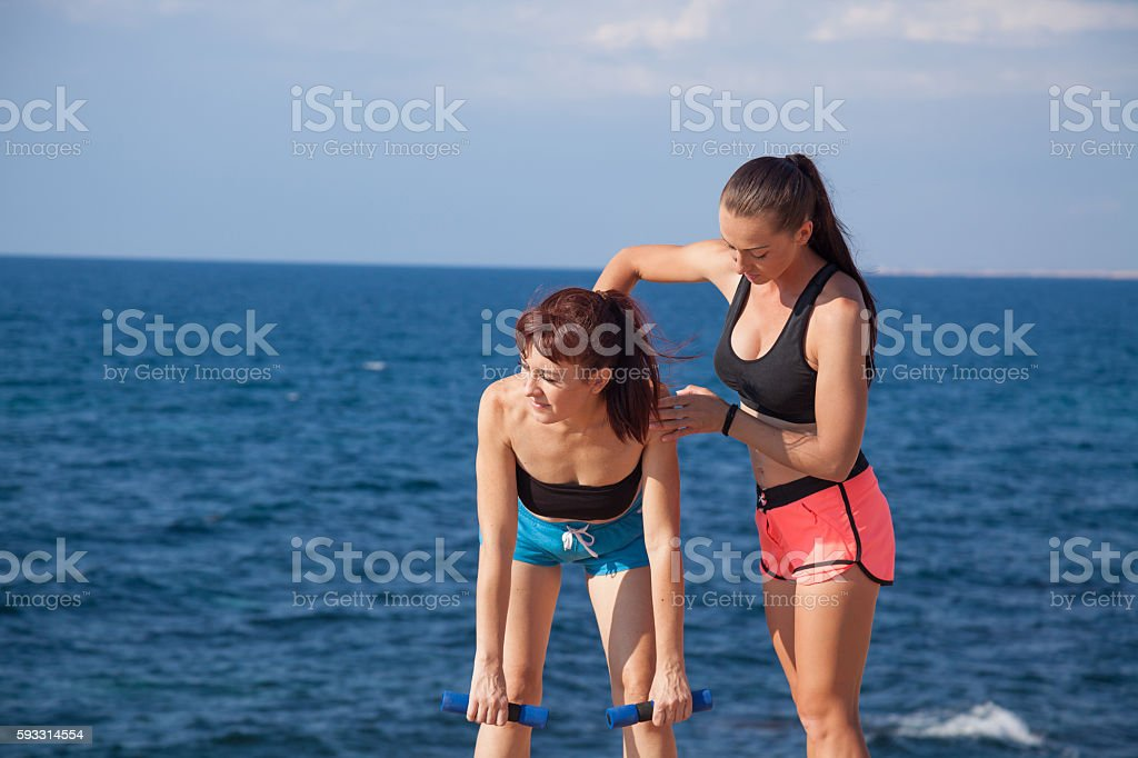 trainer helps the girl to do the exercises stock photo