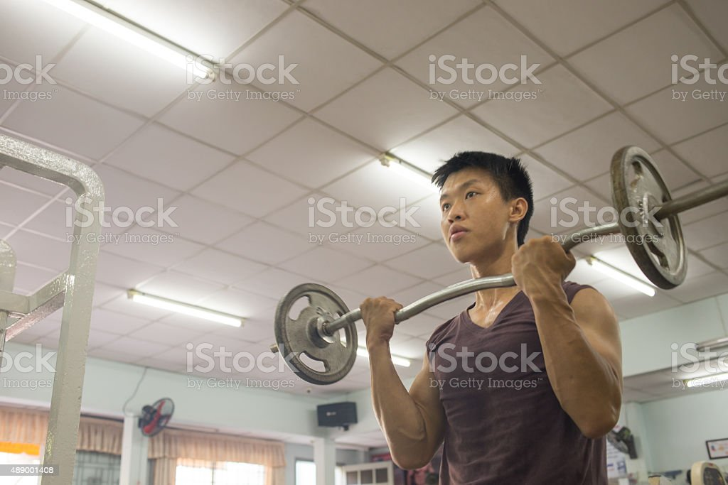 Trainer lift the weight up to build his muscle stock photo