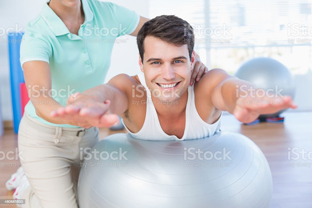 Trainer with man on exercise ball stock photo