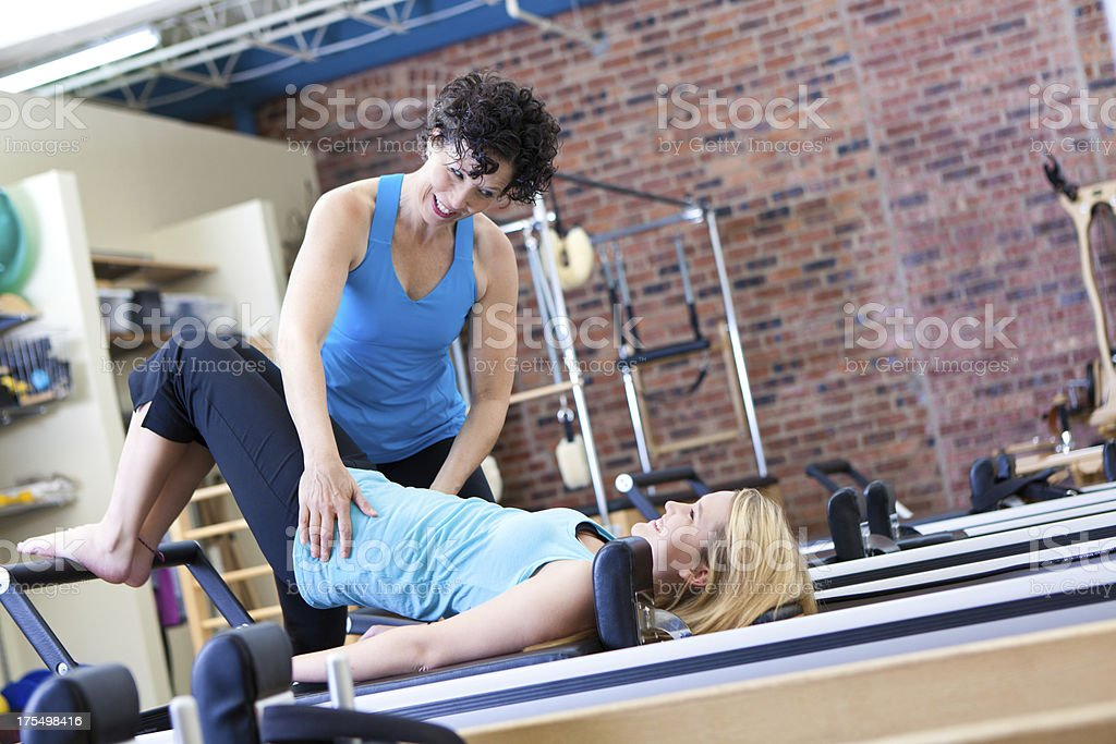 Trainer working with client on pilates strength training equipment stock photo