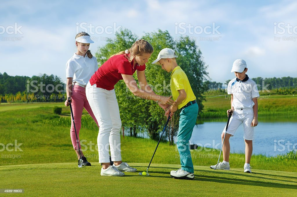 Trainer works with children at golf school stock photo
