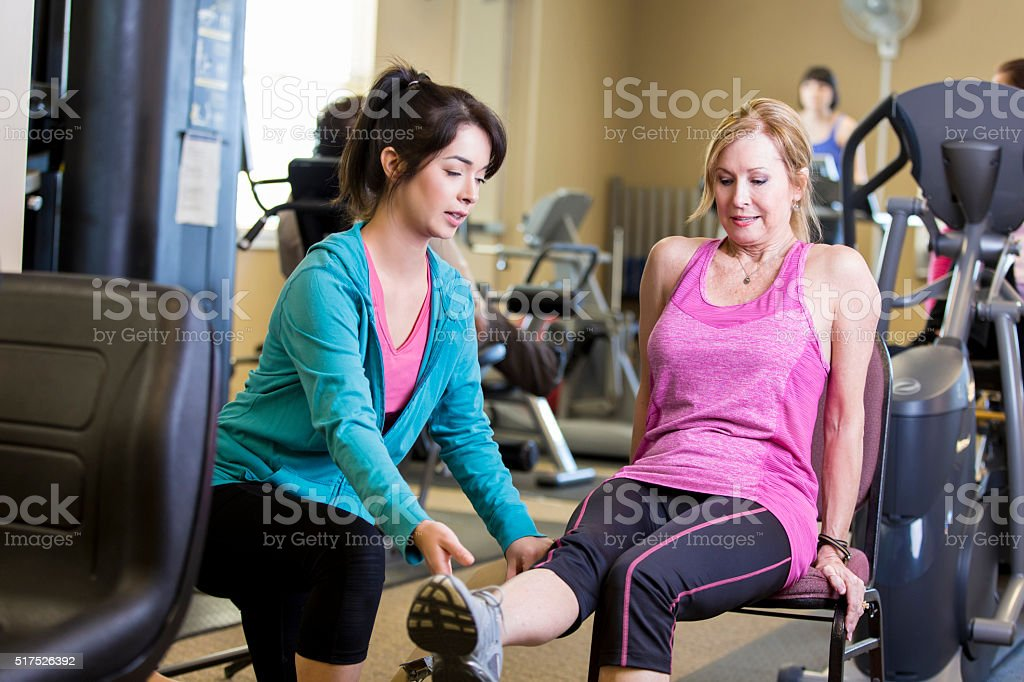 Trainer works with senior woman stock photo
