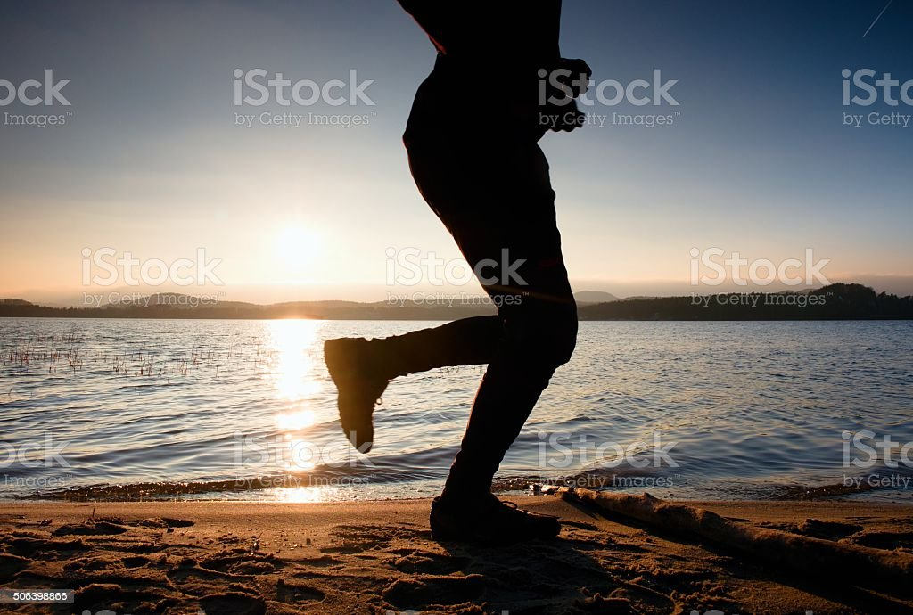 Training at sunset. Silhouette of jogger at path along lake stock photo