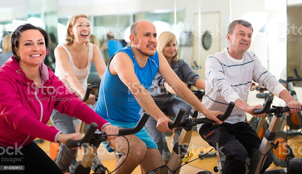 Training in sport club on fitness cycle stock photo