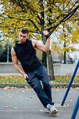 TRX training. Man Instructor at the park doing Excersise. Fitness