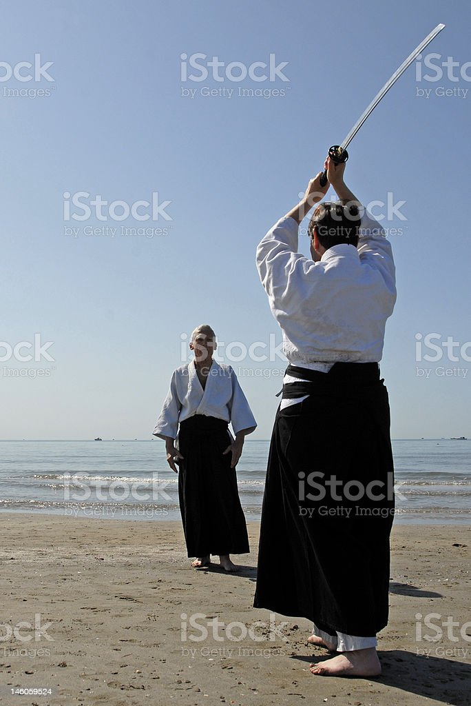 Two adults are training in Aikido on the beach