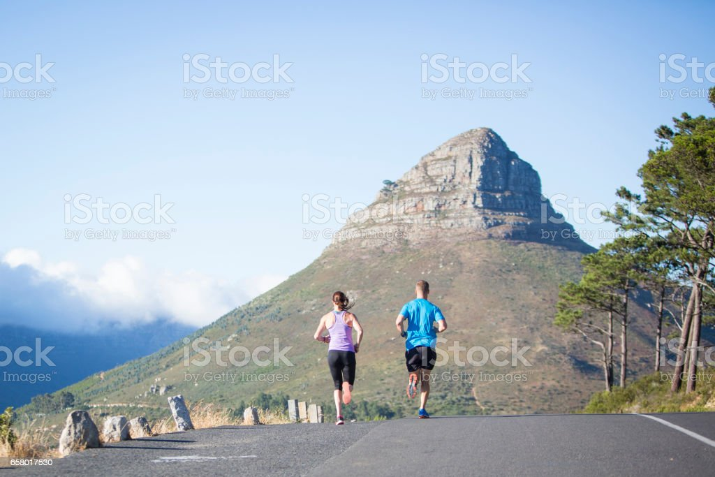 Training partners out on a morning run above the city stock photo