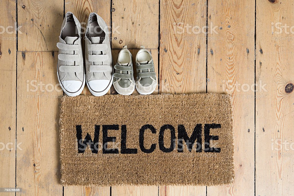 Training shoes and a welcome mat stock photo