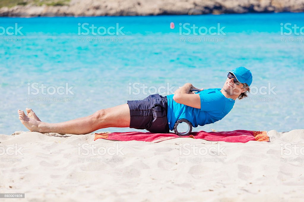 Training the abs with blackroll at the beach stock photo
