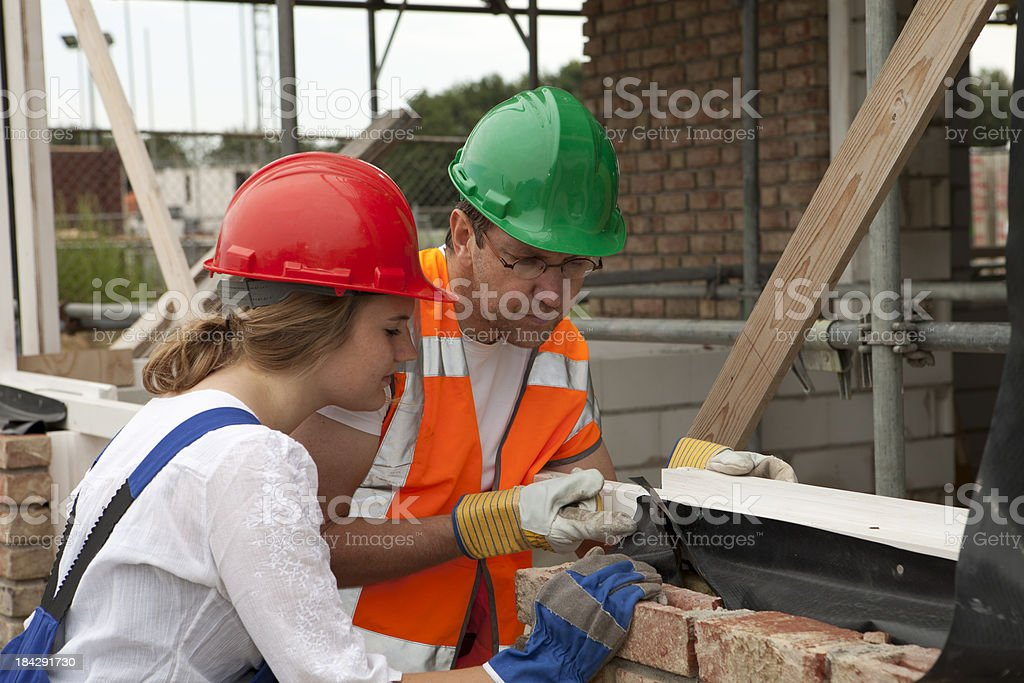Training to be a mason. Trainee making notes. royalty-free stock photo