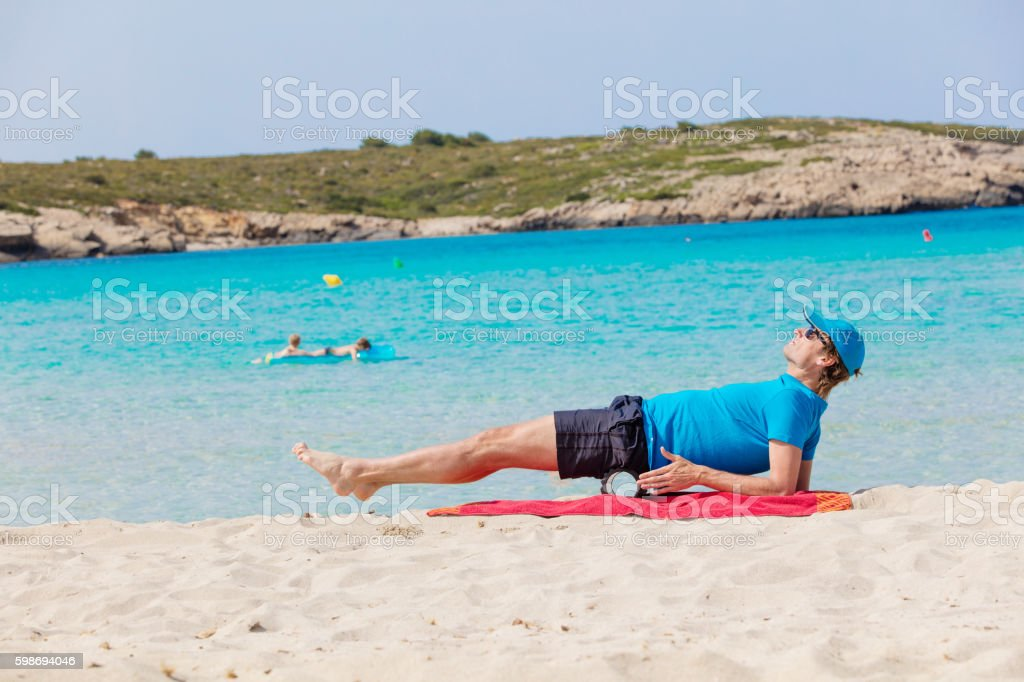 Training with blackroll at the beach stock photo