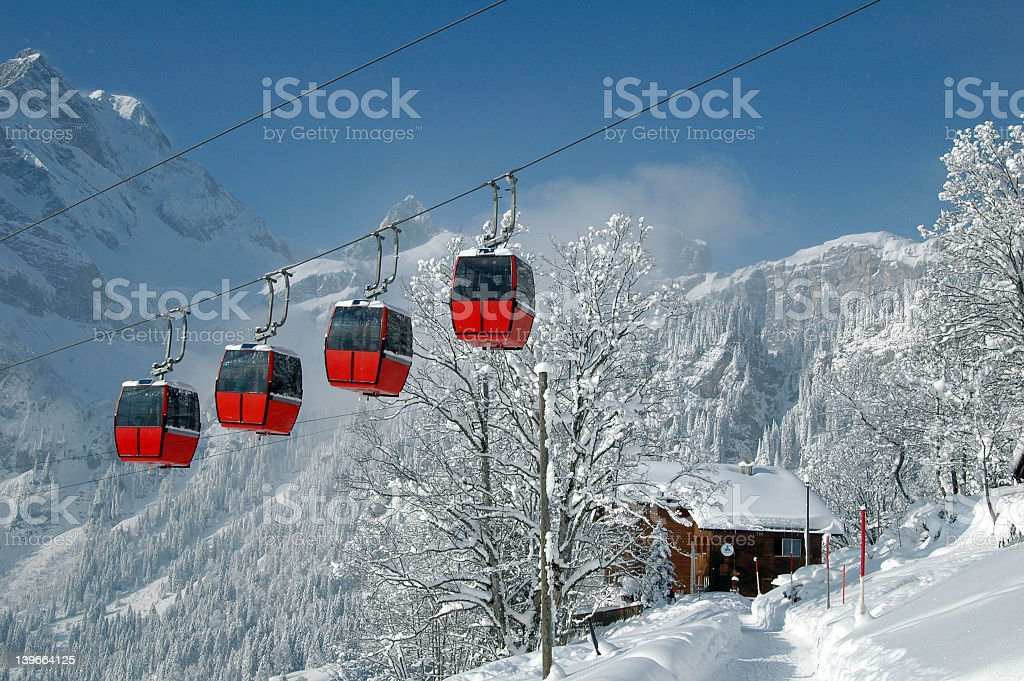 Tram cars over a snowy winter scene in the mountains stock photo