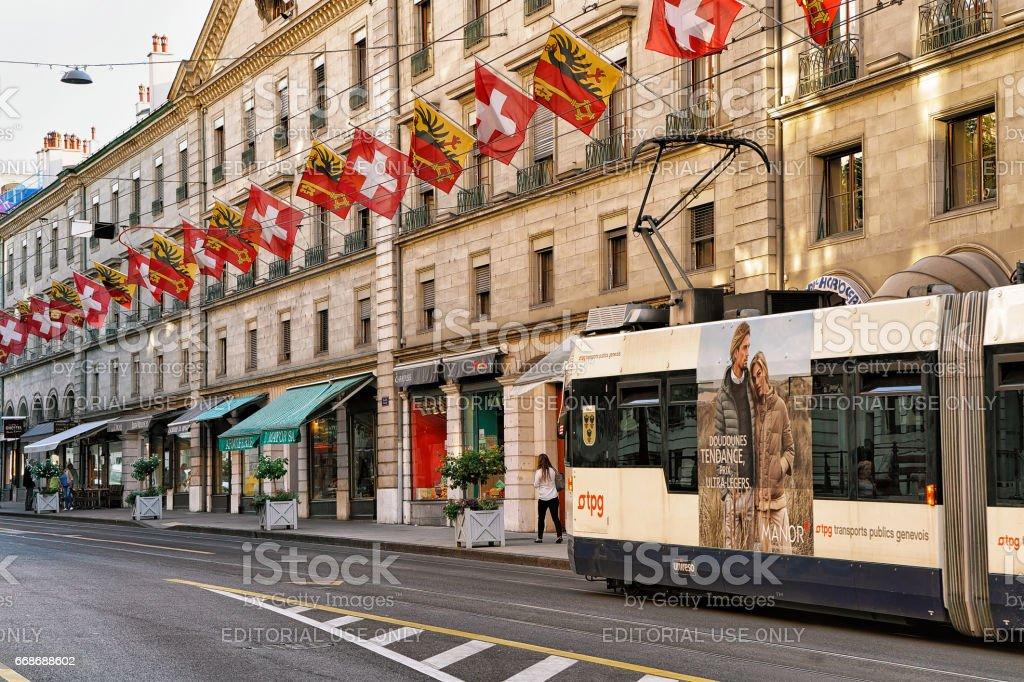 Tram in Rue Corraterie Street with flags in Geneva Swiss stock photo