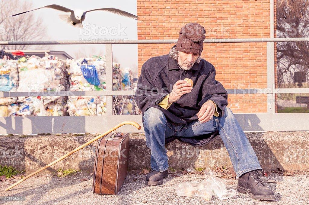 tramp eating bread sitting in landfills stock photo